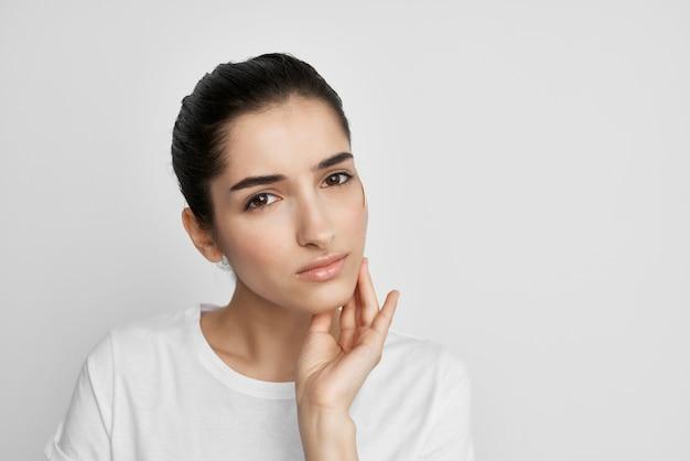 Chora kobieta w białej koszulce z negatywnym zbliżeniem bólu głowy