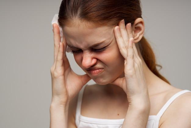 Chora kobieta w białej koszulce z szalikiem na białym tle