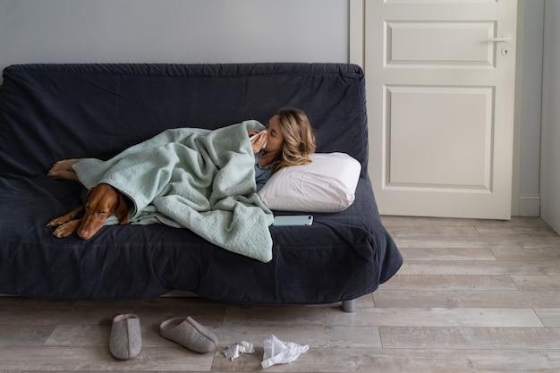 Chora kobieta w domu, leżąca w łóżku z psem wyżeł węgierski krótkowłosy, cierpiąca na alergię, objawy grypy, gorączkę