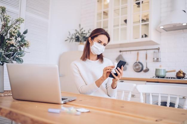 Chora kobieta w kuchni z laptopem do czyszczenia telefonu komórkowego odkażaczem ręcznym, przy użyciu waty alkoholowej podczas izolacji kwarantanny domowej covid-19 pandemiczny wirus corona. praca na odległość od koncepcji domu.