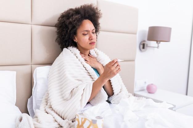 Chora kobieta w łóżku z wysoką gorączką. kobieta choruje na grypę, leżąc na łóżku patrząc na temperaturę na termometrze. chora kobieta w łóżku z wysoką gorączką.