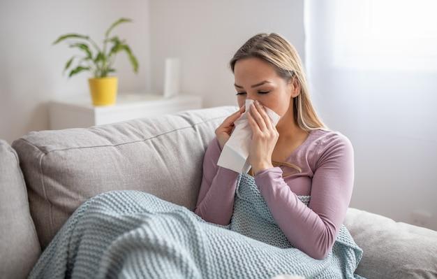 Chora kobieta wieje nos, siedząc pod kocem