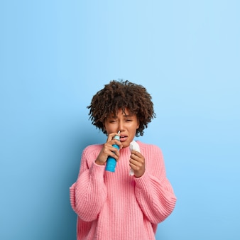 Chora kobieta z afro pozuje w różowym swetrze