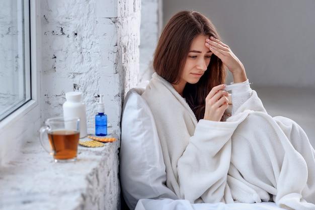 Chora kobieta z bólem głowy, bólem gardła i gorączką pokrytą kocem, mdłości