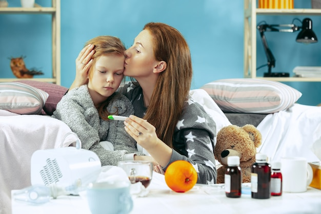 Chora kobieta z córką w domu. leczenie w domu. walka z chorobą. opieka medyczna. dom