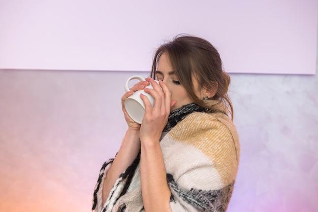 Chora kobieta z filiżanką gorącej herbaty w ciepłą kratę. koncepcja choroby i medycyny