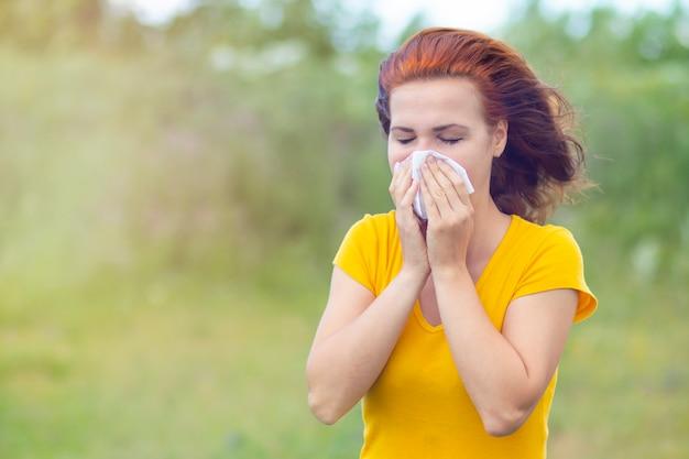 Chora kobieta z katarem na zewnątrz. kobieta wydmuchuje nos podczas epidemii grypy i przeziębienia.
