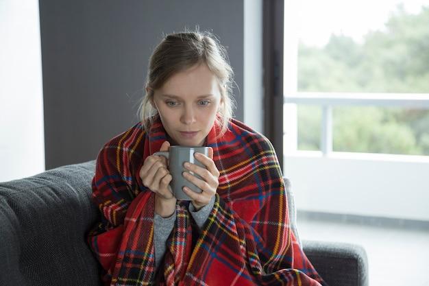 Chora kobieta z szkocką kratą trzyma kubek w ręce, patrząc w dół