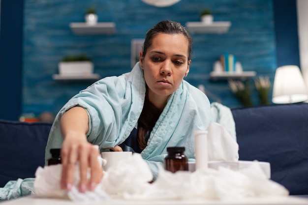 Chora kobieta zażywająca lekarstwa na sezonowe wirusy owinięta kocem trzymającym pigułki. młoda osoba rasy kaukaskiej lecząca chorobę za pomocą leczenia z powodu 19 objawów bólu związanego z temperaturą