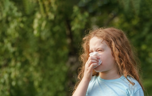 Chora mała dziewczynka kicha chusteczką na zewnątrz.
