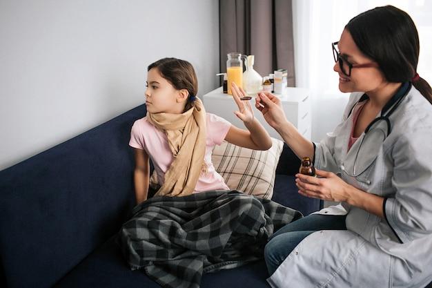 Chora mała dziewczynka nie chce brać syropu. patrzy na ścianę i trzyma dłoń blisko łyżki. rozochocony młody kobiety lekarki spojrzenie przy pacjentem i uśmiechem. trzyma łyżkę syropu.