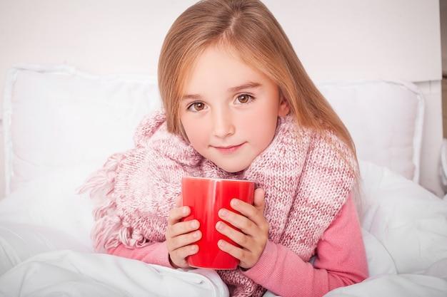 Chora mała dziewczynka z gorącą herbatą cytrynową