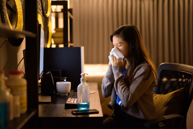 Chora młoda azjatka wydmuchuje nos chusteczką podczas pracy późno w nocy z domu