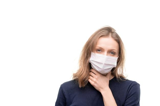 Chora młoda blond kobieta w masce ochronnej dotykając jej gardła, stojąc przed kamerą na białym tle