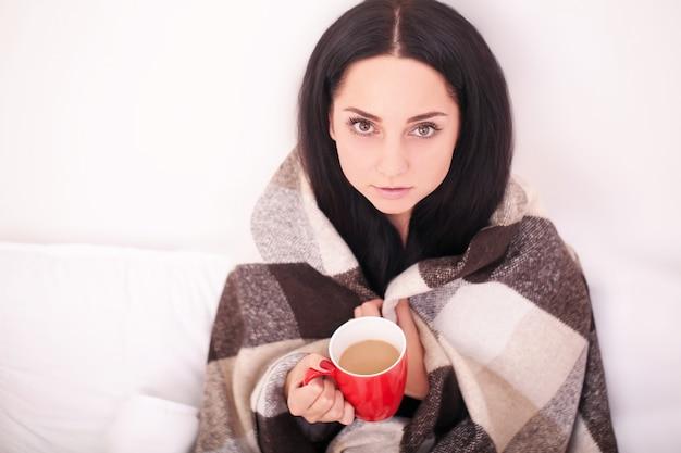 Chora młoda dziewczyna pije filiżankę ciepłej herbaty z gorączką