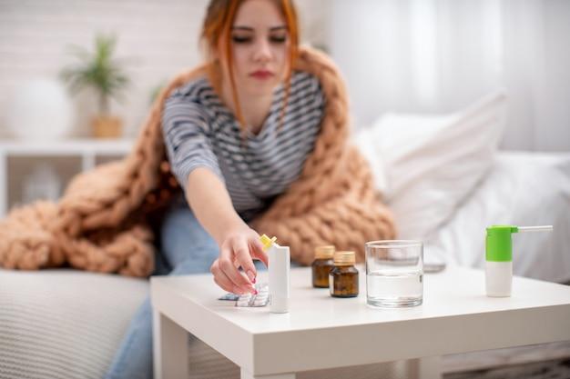 Chora młoda dziewczyna wyciąga rękę, by wziąć inhalator na alergię.