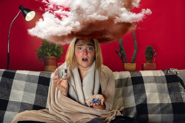 Chora młoda dziewczyna z gorączką i przeziębieniem patrzy cierpiąca w domu