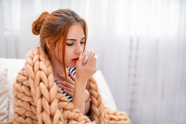 Chora młoda dziewczyna zmęczona od kaszlu w klatce piersiowej, trzymając inhalator