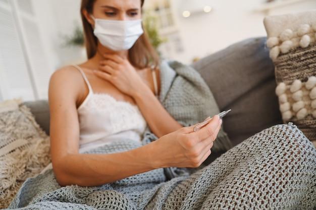 Chora młoda europejska kobieta w twarzy ochrony masce na leżance z powszechnym mienie termometrem, domowa kwarantanny ja izolacji. zakażenie wirusem koronowym. koncepcja covid-19 promuje zachowanie bezpieczeństwa w domu i ratowanie życia