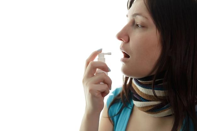 Chora młoda kobieta i spray do gardła, copyspace