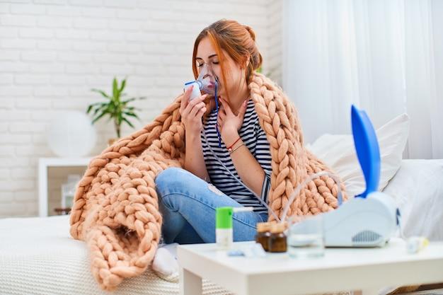 Chora młoda kobieta jest zmęczona kaszlem w klatce piersiowej, robi wdech, używając nebulizatora