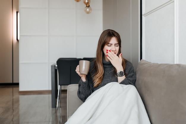Chora młoda kobieta, kaszel i kichanie na kanapie w domu z filiżanką herbaty