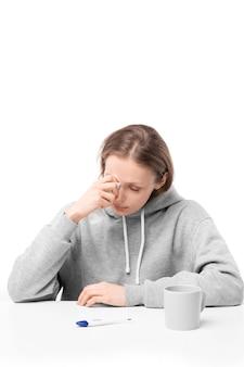 Chora młoda kobieta siedzi przy stole z termometrem cyfrowym i kubkiem i wycierając łzy, płacząc z powodu choroby