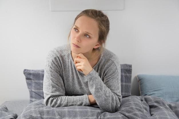 Chora młoda kobieta siedzi w łóżku, zastanawiając się nad czymś