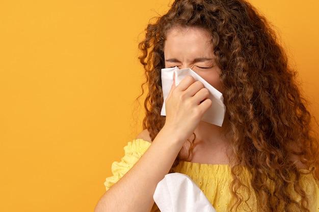 Chora młoda kobieta trzymająca chusteczkę tkankową na żółtym tle
