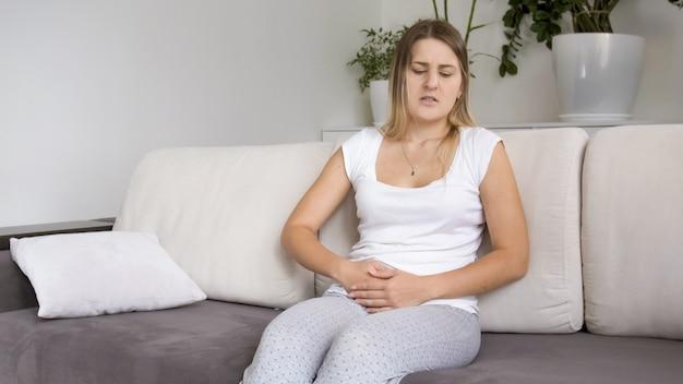 Chora młoda kobieta z bólem brzucha lub brzucha siedząca na kanapie w salonie living