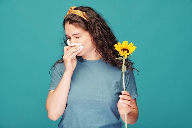 Chora młoda kobieta z chusteczką dmuchającą nos, trzymając słonecznik przed sobą na niebieskiej ścianie
