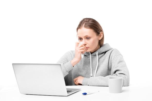 Chora młoda kobieta z dmuchaniem nosa siedząca przy biurku przed laptopem podczas pracy zdalnej w domu w okresie dystansu społecznego