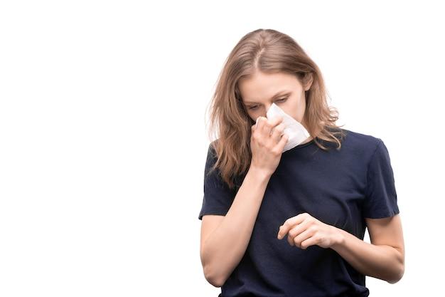 Chora młoda kobieta z nieżytem nosa, trzymając chusteczkę przez dmuchanie nosa, stojąc przed kamerą na białym tle