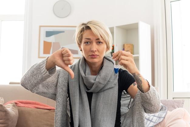 Chora młoda słowiańska kobieta z szalikiem na szyi trzymająca termometr i trzymająca kciuk w dół, siedząca na kanapie w salonie