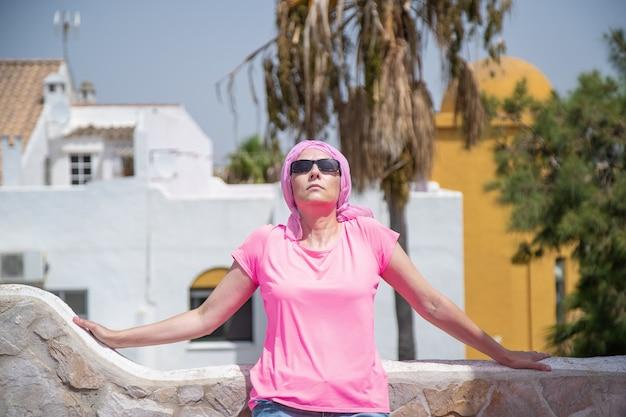 Chora na raka kobieta opalająca się na tarasie z różowym szalikiem na głowie