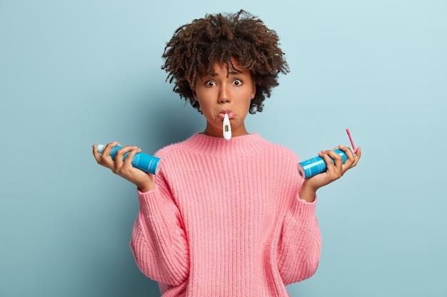Chora nieszczęśliwa ciemnoskóra kobieta mierzy temperaturę