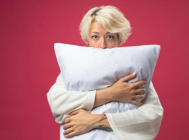 Chora niezdrowa kobieta z krótkimi włosami przytulająca poduszkę źle się czuje patrząc na kamery zmartwiona stojąc na różowym tle
