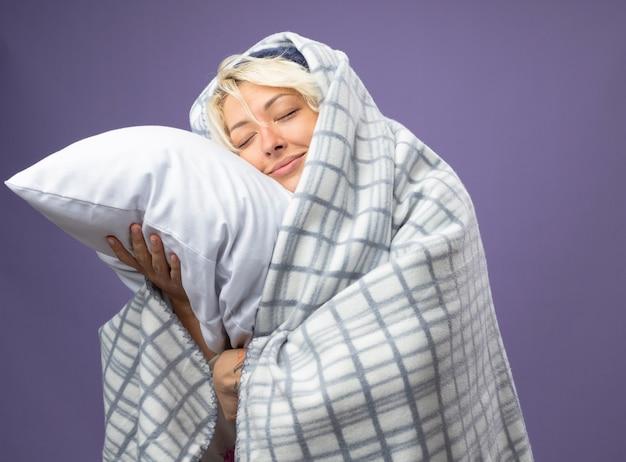 Chora niezdrowa kobieta z krótkimi włosami w ciepłym kapeluszu owinięta kocem trzymająca poduszkę opierająca głowę na poduszce z zamkniętymi oczami uśmiechnięta na fioletowym tle
