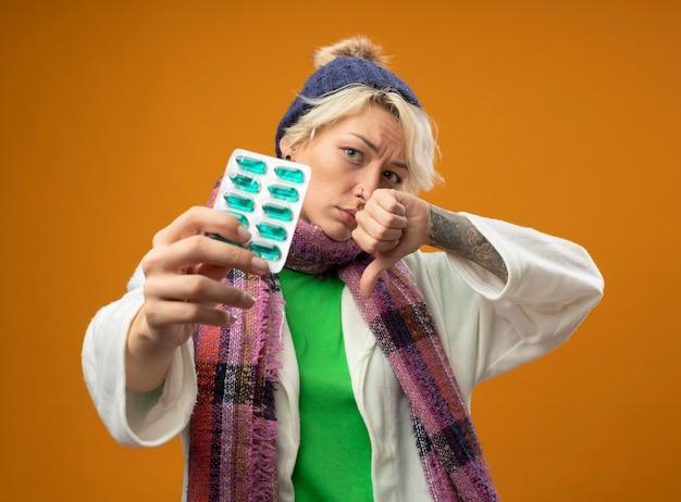 Chora niezdrowa kobieta z krótkimi włosami w ciepłym szaliku i czapce pokazująca blister z tabletkami patrząc na kamery ze smutnym wyrazem twarzy pokazujący kciuki w dół stojąc na pomarańczowym tle