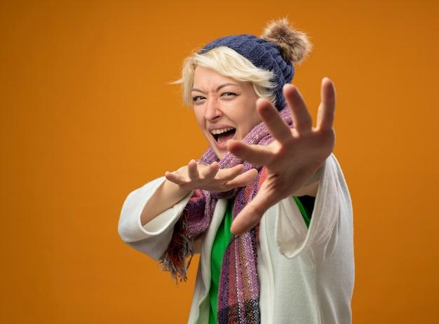 Chora niezdrowa kobieta z krótkimi włosami w ciepłym szaliku i czapce robi gest obrony z przestraszonymi rękami stojąc na pomarańczowym tle