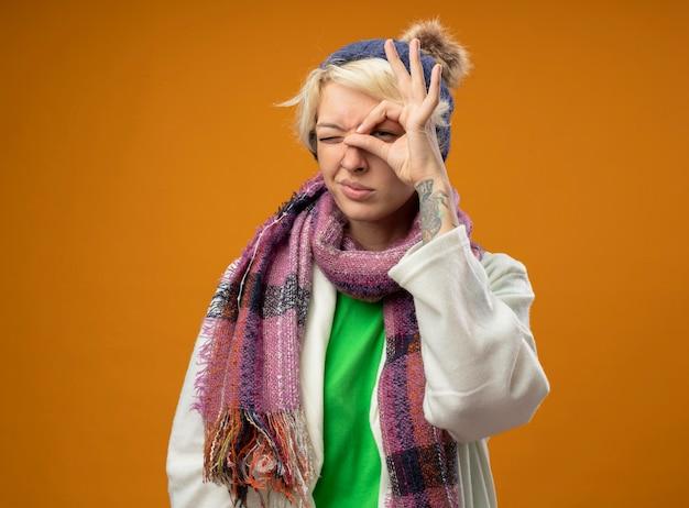 Chora niezdrowa kobieta z krótkimi włosami w ciepłym szaliku i czapce robi ok znak patrząc przez ten znak stojąc na pomarańczowym tle