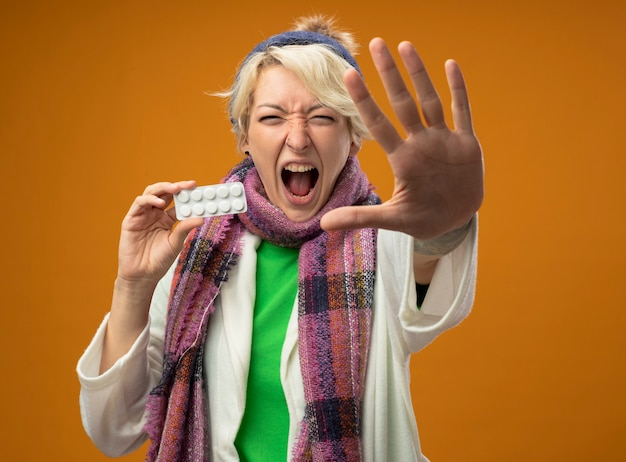 Chora niezdrowa kobieta z krótkimi włosami w ciepłym szaliku i czapce trzymająca blister z pigułkami wykonująca gest stopu z ręką krzyczącą stojącą na pomarańczowym tle