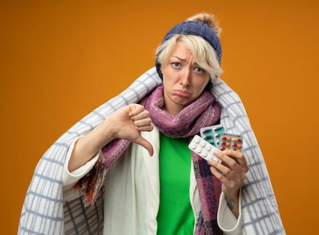 Chora niezdrowa kobieta z krótkimi włosami w ciepłym szaliku i czapce zawinięta w koc trzyma pigułki patrząc na kamery nieszczęśliwa i smutna, pokazując kciuki w dół stojąc na pomarańczowym tle