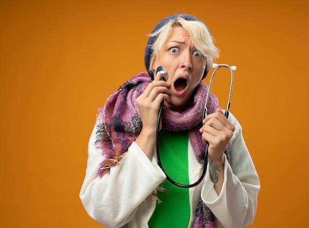 Chora niezdrowa kobieta z krótkimi włosami w ciepłym szaliku i czapce ze stetoskopem słuchająca jej pulsu wyglądająca na zmartwioną stojącą na pomarańczowym tle