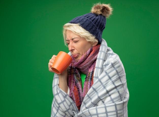 Chora niezdrowa kobieta z krótkimi włosami w ciepłym szaliku i czapce źle się czuje owinięta kocem, pije gorącą herbatę z zirytowanym wyrazem twarzy, stojąca nad zieloną ścianą