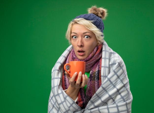 Chora niezdrowa kobieta z krótkimi włosami w ciepłym szaliku i czapce źle się czuje owinięta kocem trzymając kubek gorącej herbaty patrząc na aparat zaskoczony stojąc na zielonym tle