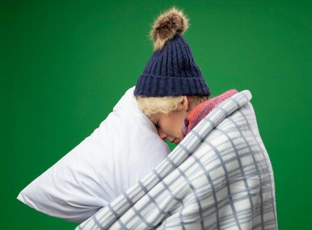 Chora niezdrowa kobieta z krótkimi włosami w ciepłym szaliku i czapce źle się czuje owinięta kocem trzymając poduszkę bokiem opierając głowę na poduszce na zielonym tle