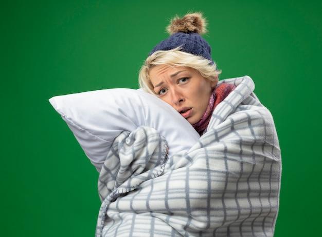 Chora niezdrowa kobieta z krótkimi włosami w ciepłym szaliku i czapce źle się czuje owinięta kocem trzymając poduszkę patrząc na kamerę ze smutnym wyrazem twarzy stojącej na fioletowym tle