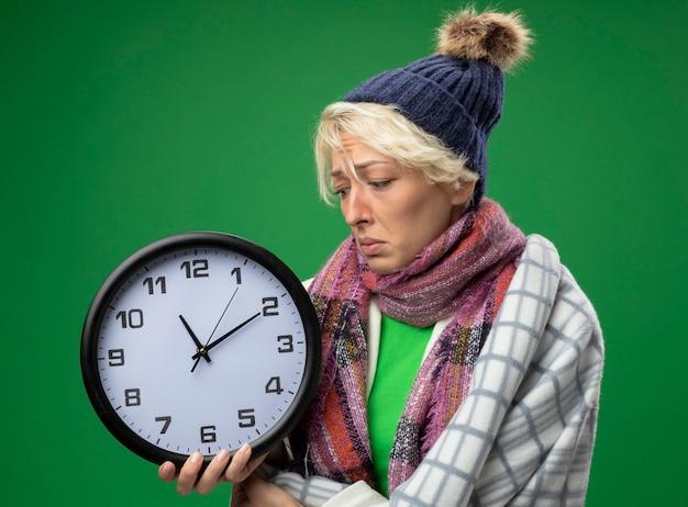 Chora niezdrowa kobieta z krótkimi włosami w ciepłym szaliku i czapce źle się czuje owinięta kocem trzymając zegar ścienny patrząc na niego ze smutnym wyrazem twarzy na zielonym tle