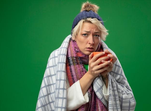 Chora niezdrowa kobieta z krótkimi włosami w ciepłym szaliku i czapce źle się czuje owinięta w koc trzymający kubek gorącej herbaty stojąca na zielonym tle